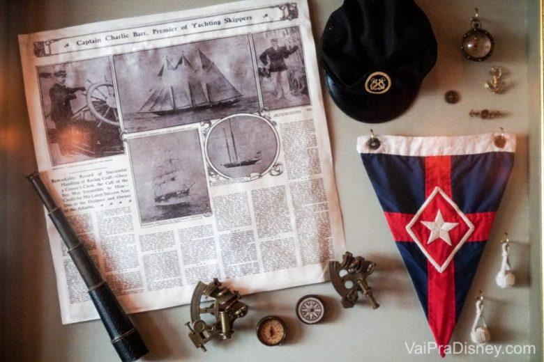 Foto dos pequenos detalhes da decoração dentro do tema náutico de todo o hotel, como uma bandeira, uma luneta e um recorte de jornal.