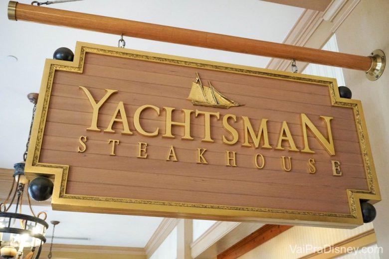 Foto da placa no restaurante Yachtsman Steakhouse, em madeira clara com detalhes dourados
