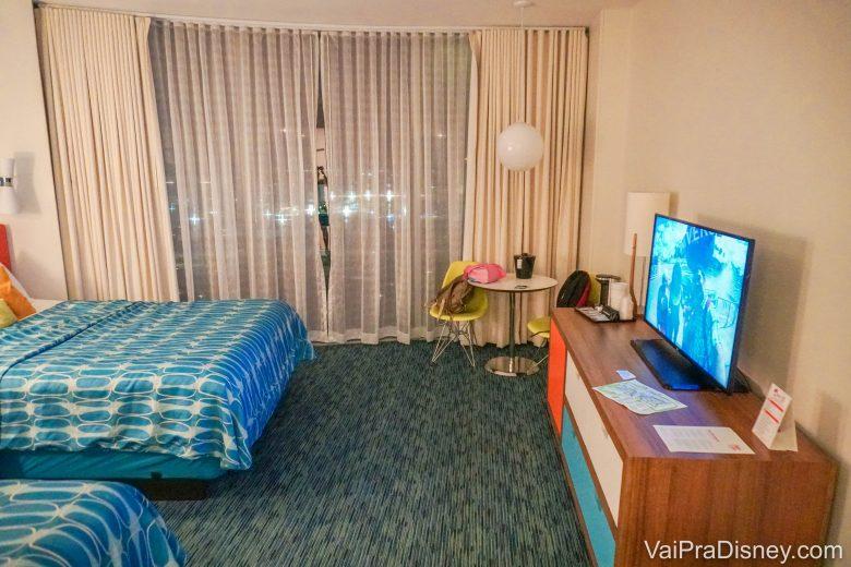 Foto do quarto padrão do Cabana Bay, com 2 camas, móvel com TV e carpete, bastante espaçoso