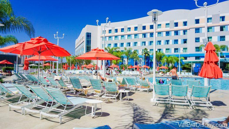 Foto da piscina do Endless Summer, um dos hotéis da Universal em Orlando. As cadeiras de praia são azuis e os guarda-sóis são alarajados.