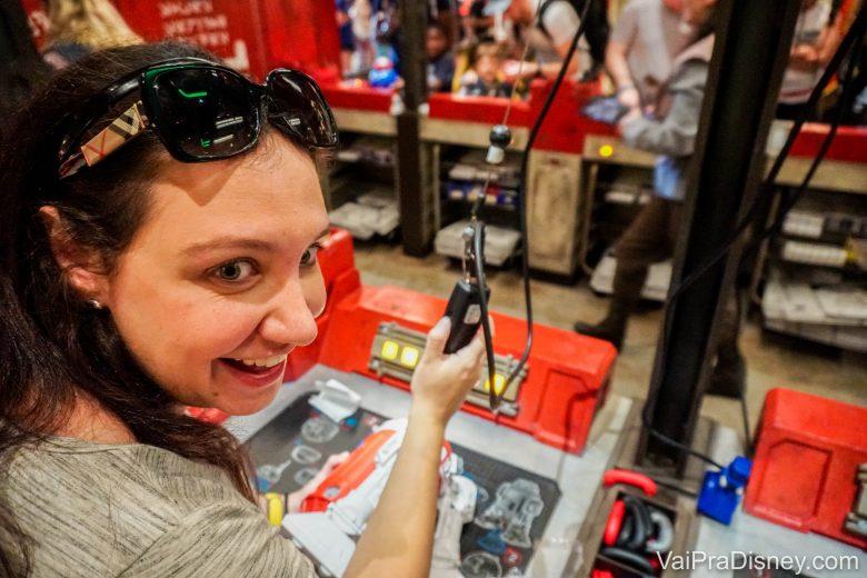 Foto da Renata sorrindo, com o controle remoto na mão, experimentando seu novo droid