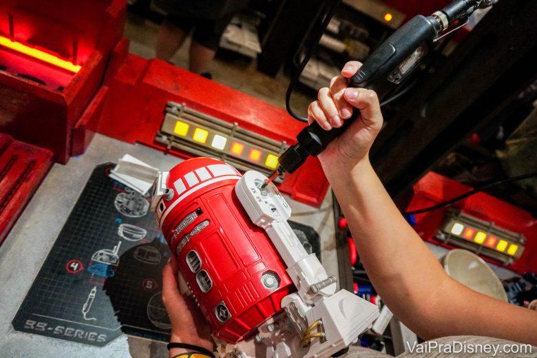 Foto da Renata ajustando uma peça no seu droid vermelho com uma ferramenta