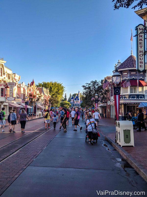 Foto do castelo da Bela Adormecida na Disneyland, ao fundo da Main Street movimentada
