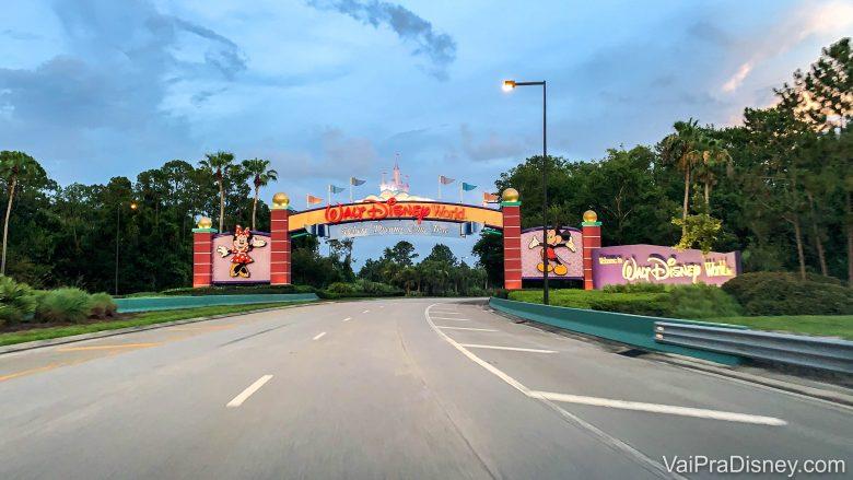 Foto do portal de entrada do complexo da Disney em Orlando, com o castelo no centro da placa que diz Walt Disney World e o Mickey e a Minnie de cada um dos lados