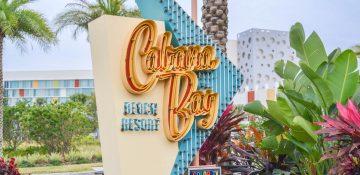 Foto da placa na entrada do Cabana Bay, com o nome do hotel em laranja, fundo azul e o mesmo estilo vintage da decoração interna