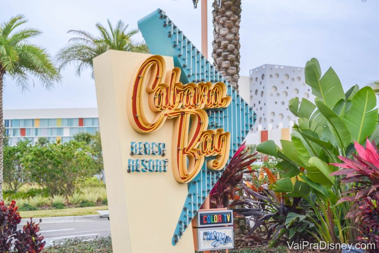 """Foto da placa no hotel Cabana Bay, da Universal, com o nome do local """"Cabana Bay Beach Resort"""" escrito em amarelo e azul."""