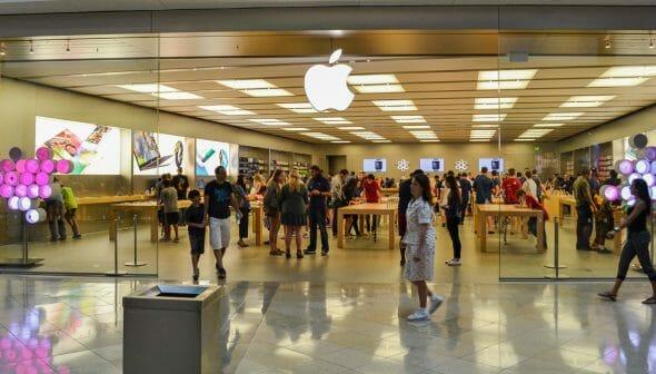 Imagem da fachada da loja da Apple em Orlando. Várias pessoas estão dentro da loja e outras estão passando no corredor.