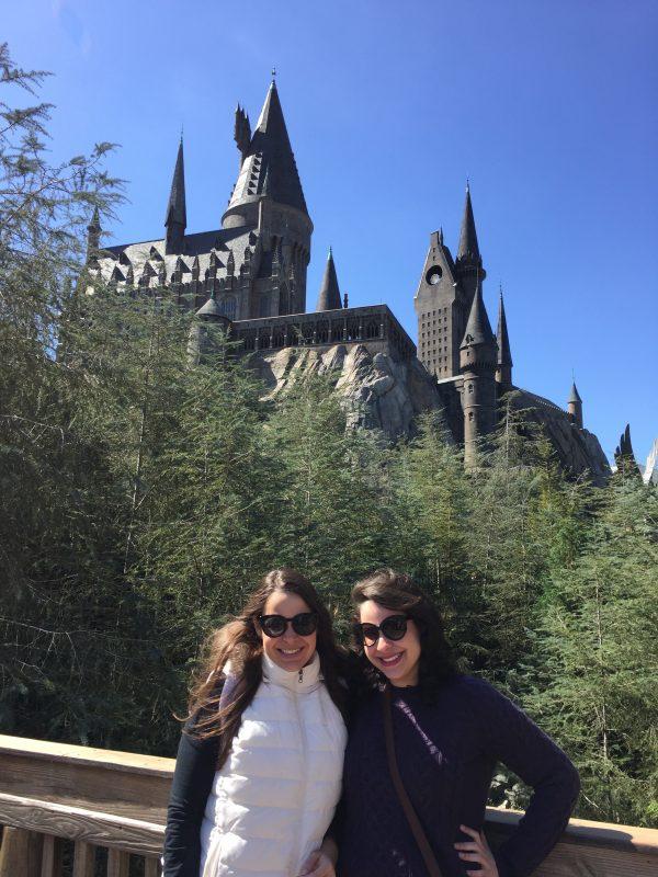 Bia e Julinha: quem é quem? Valeeeendo! Foto da Bia e da Julia, da equipe do VPD, em frente ao castelo de Hogwarts na Universal em um dia de céu azul