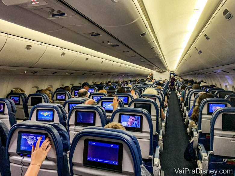 Imagem do interior de um avião. É possível ver a parte de trás de diversas fileiras de poltronas, com as telas acopladas atrás.