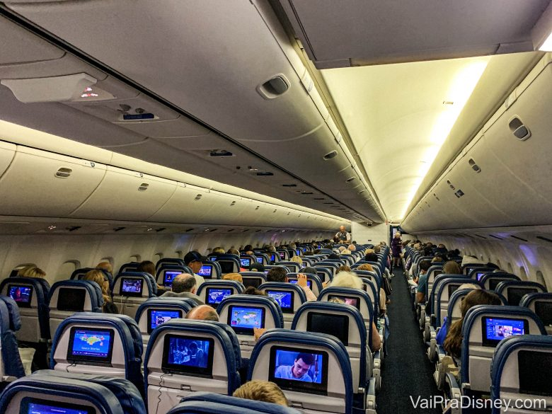 Foto do corredor do avião, visto de trás, mostrando as pequenas TVs na traseira de cada poltrona