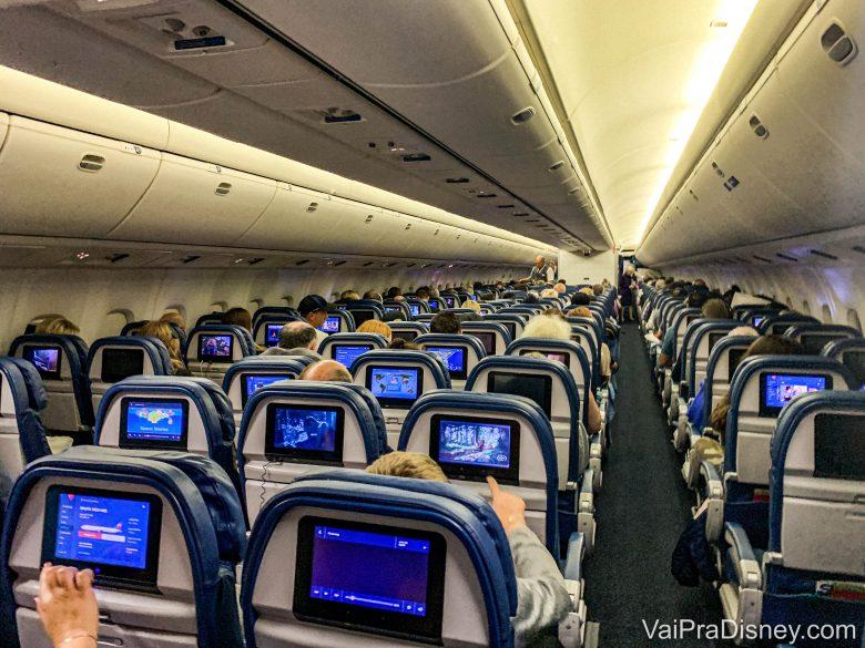 Foto do corredor no interior de um avião. É possível ver a parte de trás de diversas fileiras de poltronas, com as telas acopladas atrás. No avião, vale ter um cuidado redobrado com a higiene em tempos de coronavírus.