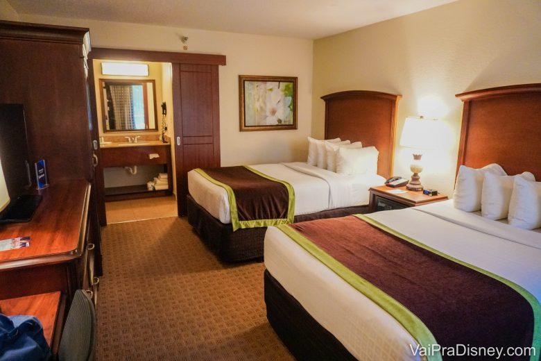 Entenda a política de cancelamento do seu hotel se for reservar. Foto do quarto do Clarion Inn Lake Buena Vista, com duas camas de casal e a pia do banheiro à vista no fundo.