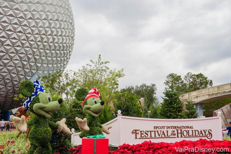 Entrada do Festival of the Holidays no Epcot. Duas topiárias do Mickey e da Minnie estão em frente à bola do Epcot,com chapéuzinhos temáticos e caixas de presente. O Festival of the Holidays 2020 acontece entre 27 de novembro e 30 de dezembro.
