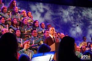 Imagem do Neil Patrick Harris em frente ao coral do Candlelight Processional, a cantata de Natal do Epcot