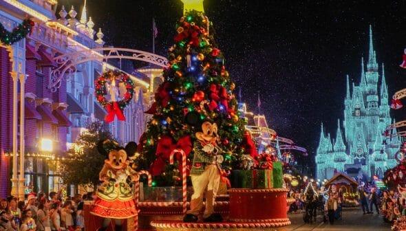 Imagem da parada de Natal do Magic Kingdom. A Minnie e o Mickey estão com roupas temáticas em um carro que possui uma árvore de Natal toda decorada.