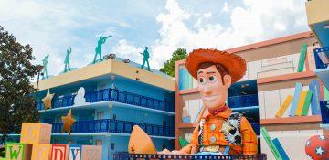 Foto do hotel Disney's All Star Movies, na área do Toy Story. Há uma réplica do Woody gigante rodeado de brinquedos, ao lado do prédio, que é azul.