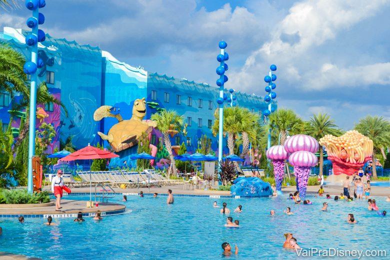 A imagem mostra visitantes na piscina do hotel da Disney, o Art of Animation. A decoração é colorida, o prédio ao fundo é azul e a tartaruga do filme Procurando Nemo é parte da decoração.