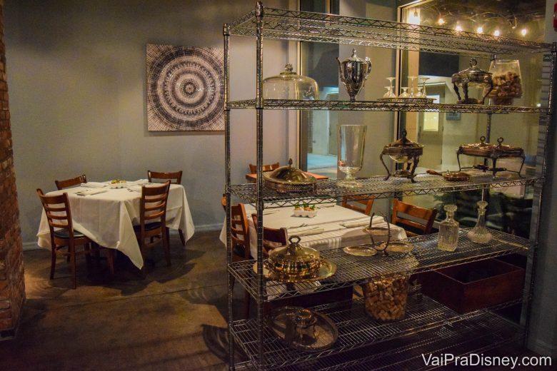 Foto da decoração em estilo industrial do restaurante, com estantes de metal e quadros