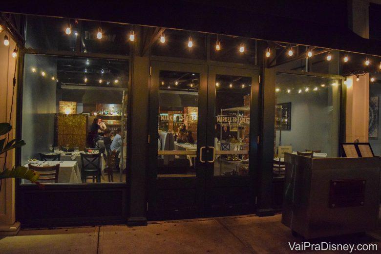 Foto da entrada discreta do Market to Table, com portas de vidro e luzes penduradas