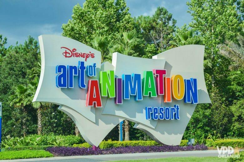 Imagem da placa do hotel Art of Animation, que tem letras coloridas e plantas verdes ao fundo.