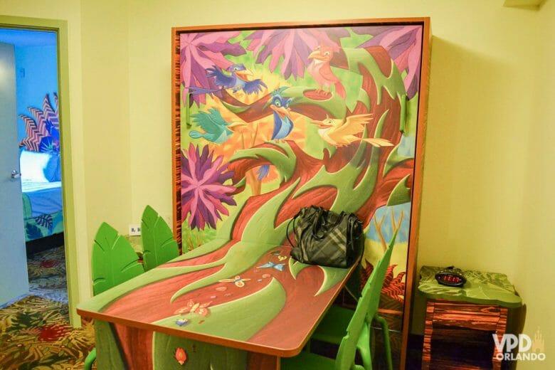 Mesa que vira cama no quarto do Rei Leão, na versão mesa mesmo, fechada. A mesa é decorada com os pássaros do filme em uma árvore marrom e verde.