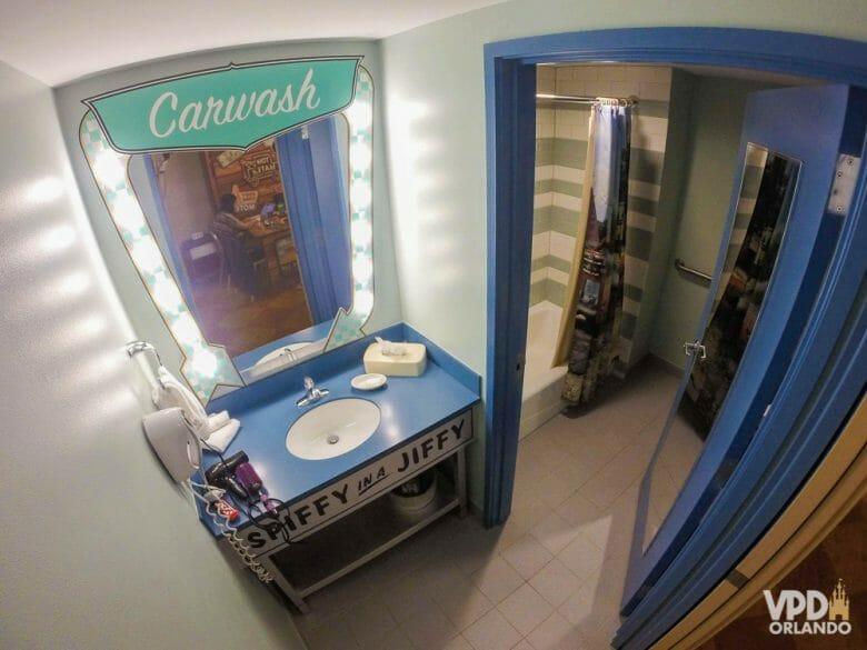 Foto do banheiro do quarto da área de Carros no hotel Art of Animation. Há um espelho com luzes ao redor, e as portas e a pia são pintadas de azul.