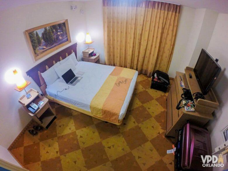 Foto do quarto principal da suíte do Carros no hotel Art of Animation. O chão é quadriculado, as cortinas são amarelas e a cama é de casal, em frente a uma cômoda com TV.