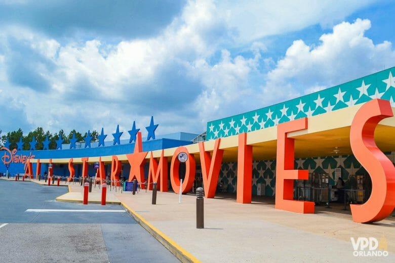 A foto mostra a placa do hotel All Star Movies. As letras são alaranjadas, há estrelas azuis no fundo e as paredes também tem estrelas.