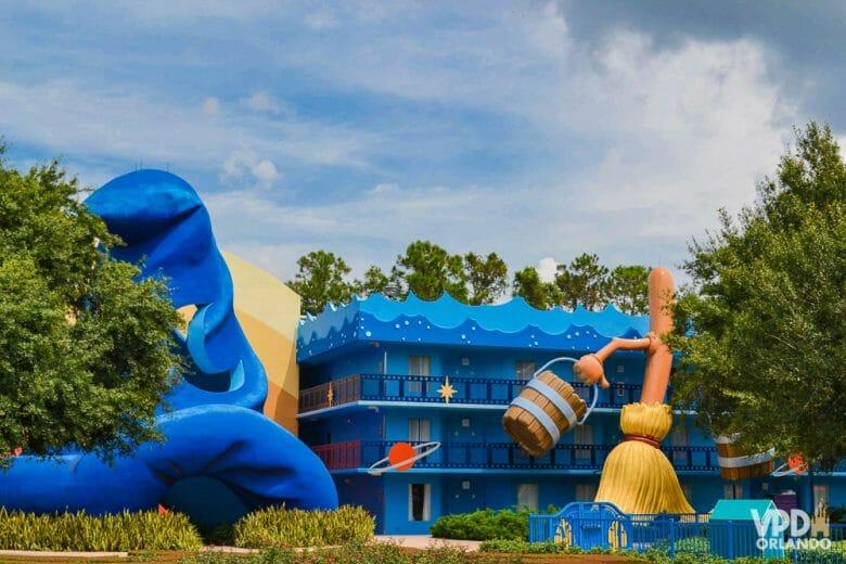 Foto da área do Fantasia, também no hotel All Star Movies. Há o icônico chapéu de feiticeiro do Mickey, e o prédio é azul.