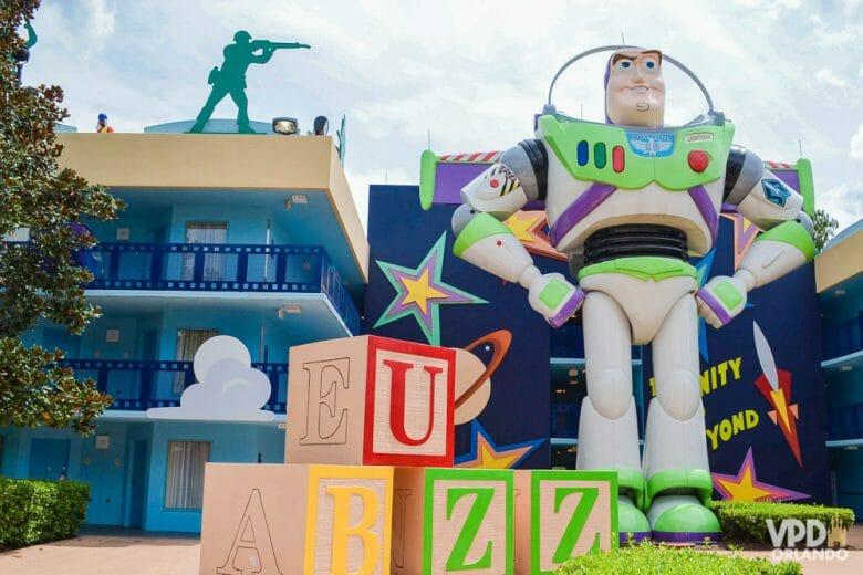 Foto do Buzz gigante na decoração da área do Toy Story do hotel All Star Movies, ao lado de brinquedos.