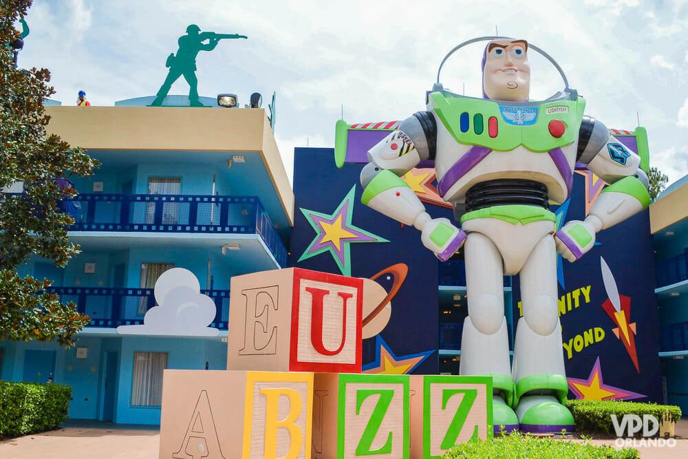 Boneco do Buzz Lighyear em frente a um prédio azul do All-Star Movies. Blocos com as letras BUZZ estão ao lado dele.