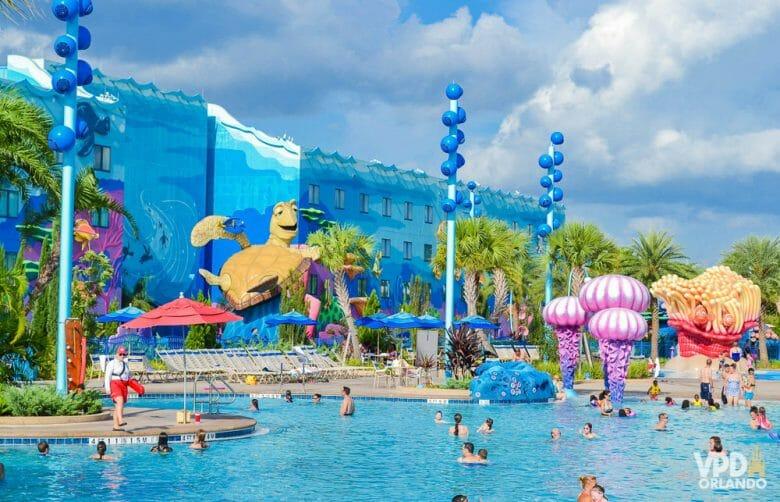 A imagem mostra visitantes na piscina do hotel Art of Animation. A decoração é colorida, o prédio ao fundo é azul e a tartaruga do filme Procurando Nemo é parte da decoração.