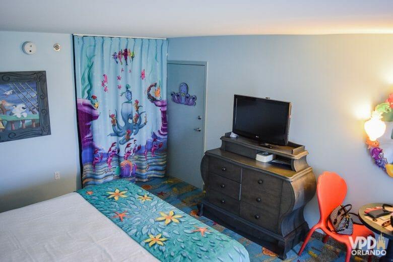 Foto do interior do quarto da Pequena Sereia no Art of Animation. É possível ver a cama e a cortina, com decorações de fundo do mar, a TV sobre um móvel, uma cadeira laranja e um quadro na parede.