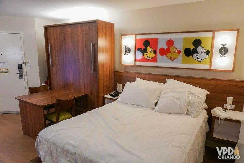 Imagem do quarto reformado do hotel Pop Century. Há uma cama de casal com lençóis brancos e um quadro com três Mickeys em cores diferentes.
