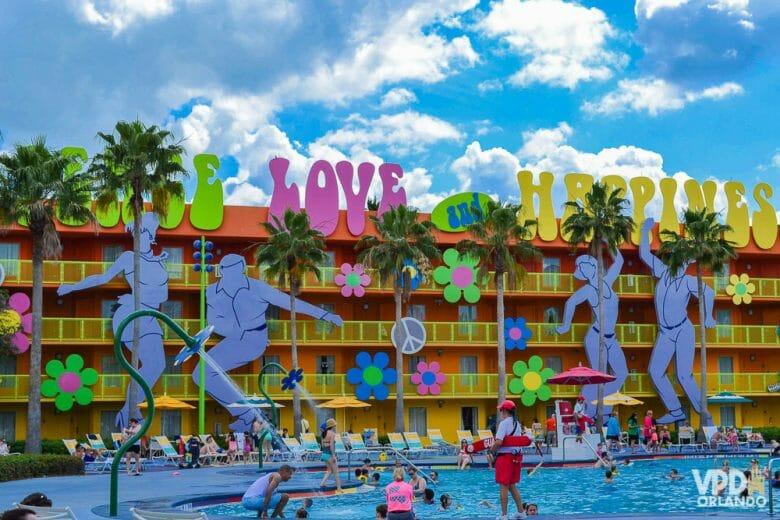 """Foto da piscina do hotel Pop Century, que tem decoração dos anos 70, com as palavras """"peace"""", """"love"""" e """"happiness"""" em grandes letras coloridas e pessoas dançando."""