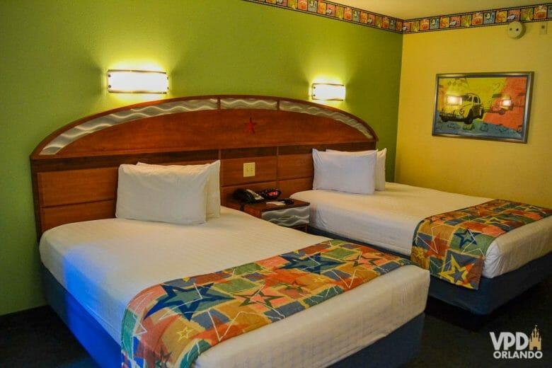 A imagem mostra os quartos antigos do hotel All Star. Há duas camas, com uma colcha de estrelas colorida, um quadro na parede, e as paredes são pintadas de verde e amarelo.