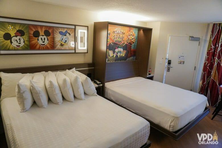 Imagem de um dos quartos reformados do All-Star, com duas camas, uma delas com 5 travesseiros apoiados, e quadros dos personagens da Disney na parede. Muita gente fica em dúvida se vale a pena trocar de hotel durante a viagem.