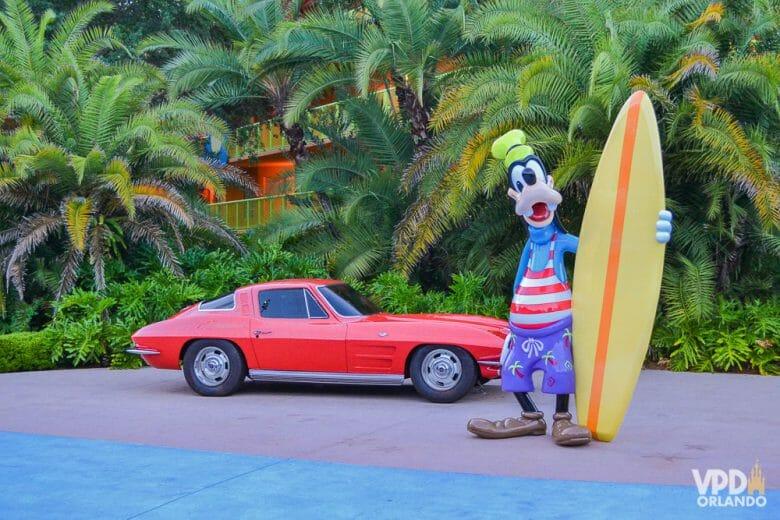 Foto do Pateta com roupas de praia e uma prancha de surf, ao lado de um carro antigo, na decoração do hotel Pop Century