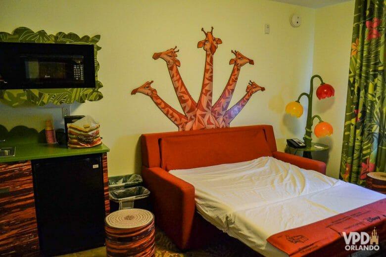 Imagem do quarto do Rei Leão no hotel Art of Animation. Há um desenho com girafas atrás do sofá-cama, uma luminária colorida e uma cortina estampada, além de parte da mini-cozinha.
