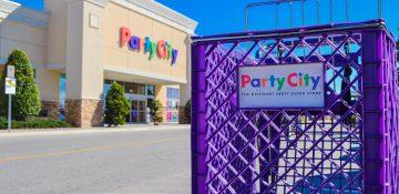 Foto do exterior da loja Party City em Orlando, com seu letreiro multicolorido ao fundo e um carrinho de compras roxo em primeiro plano, com o mesmo letreiro em versão menor