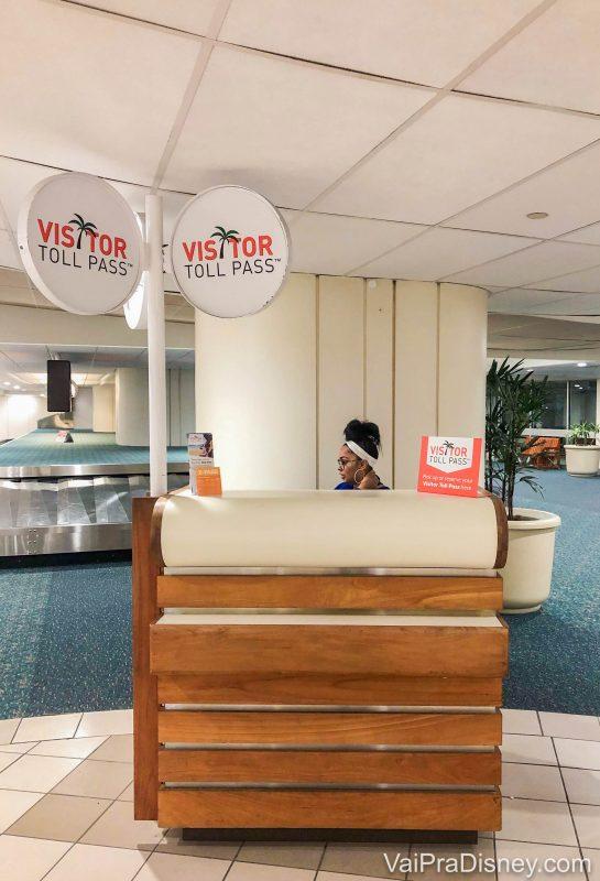 """Foto do balcão do Visitor Toll Pass, com uma atendente atrás e as placas dizendo """"Visitor Toll Pass"""""""