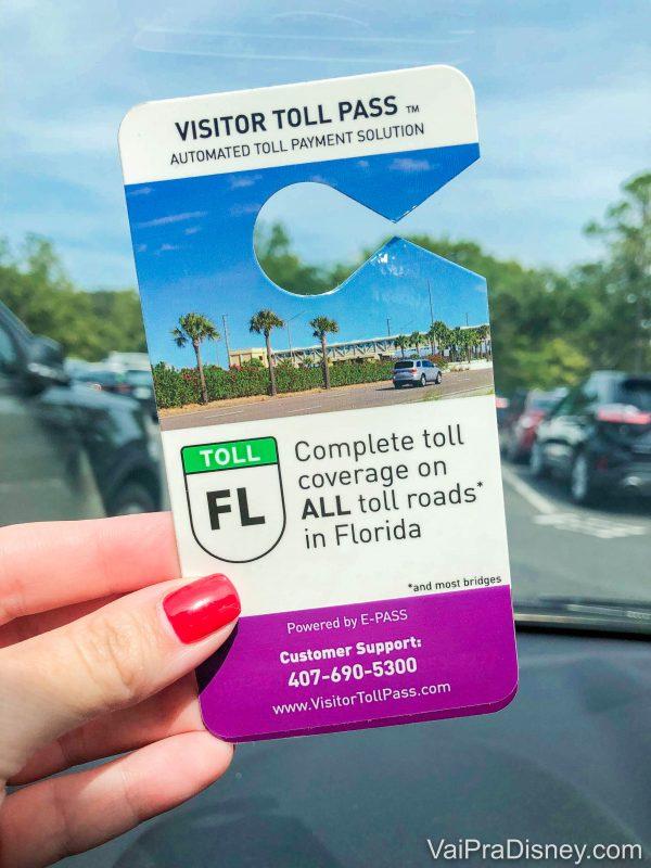 Foto de uma mão segurando o Visitor Toll Pass para ser colocado no carro.