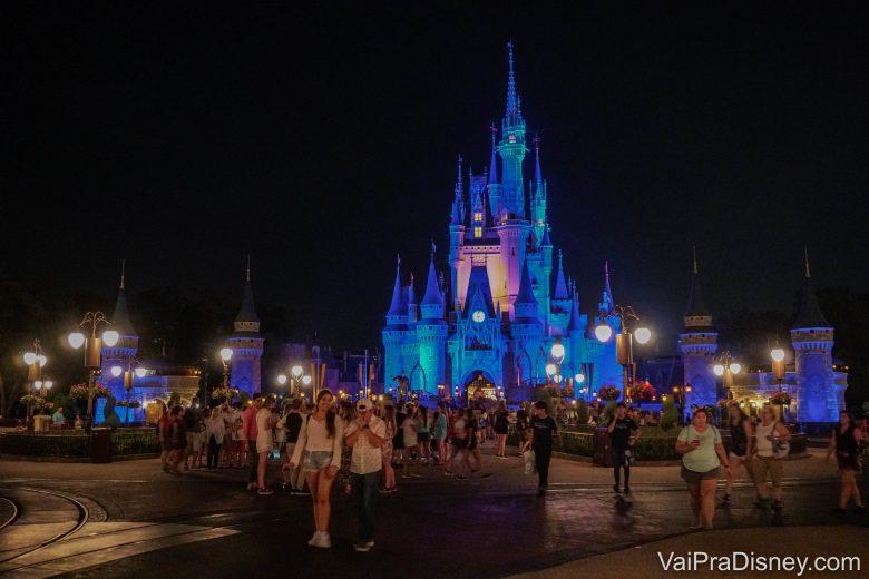 Foto do castelo da Cinderela iluminado em azul à noite e diversos visitantes circulando pelo Magic Kingdom