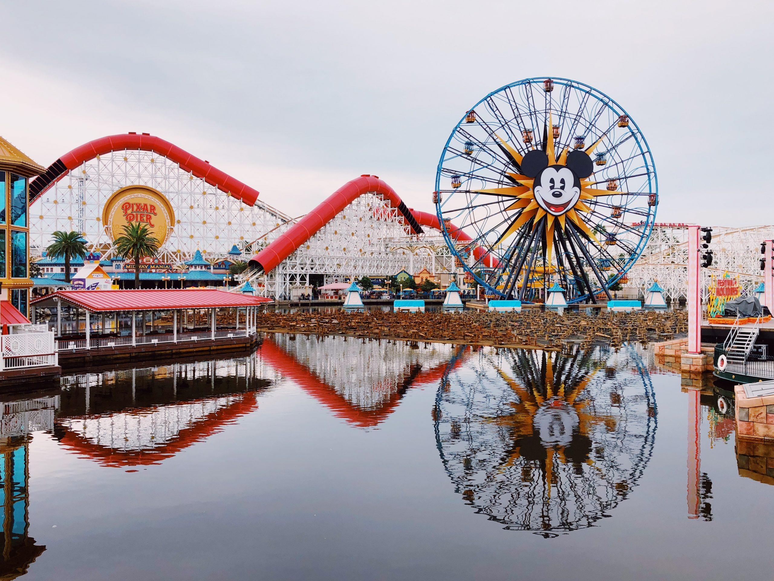 Foto do parque Disney's California Adventure, na Disneyland, mostrando a roda gigante com o rosto do Mickey e o lago que fica em frente a ela.