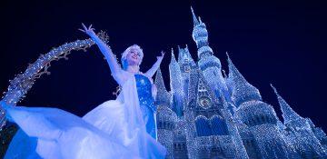 Foto da rainha Elsa em frente ao castelo da Cinderela no Magic Kingdom, iluminado em tons de azul contra o céu escuro.