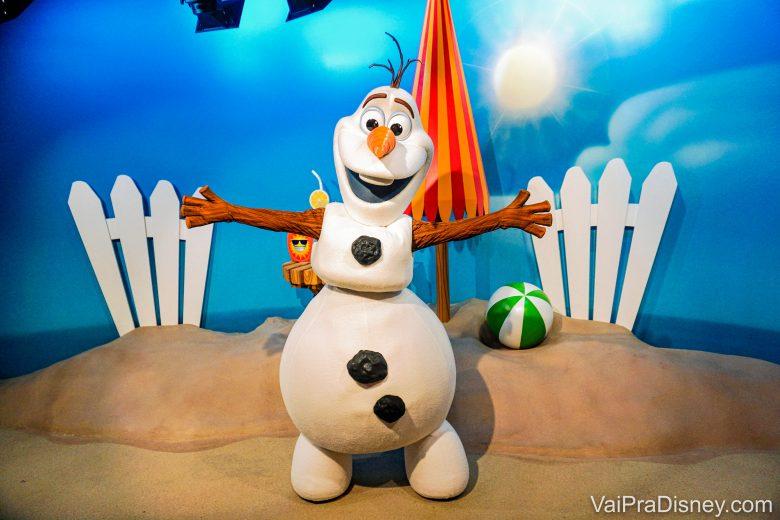 Quem não quer dar um abraço quentinho no Olaf? Foto do Olaf em um fundo de praia, posando para a foto com os braços abertos.