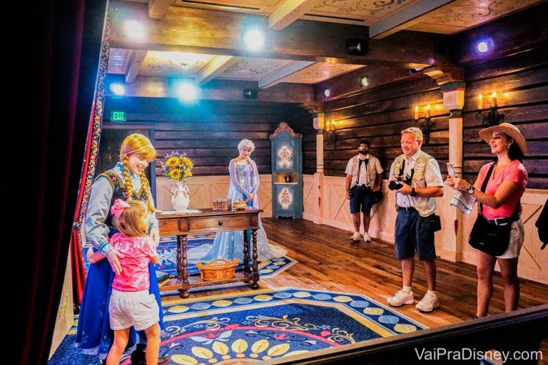 Encontro com a Anna e Elsa no Epcot, ainda com as roupinhas antigas. Foto de duas crianças abraçando a princesa Anna no cenário norueguês em que ela posa para fotos com visitantes no Epcot.