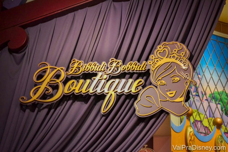 Foto da placa na entrada da Bibbidi Bobbidi Boutique, que é lilás e dourada, com um desenho do rosto da Cinderela.
