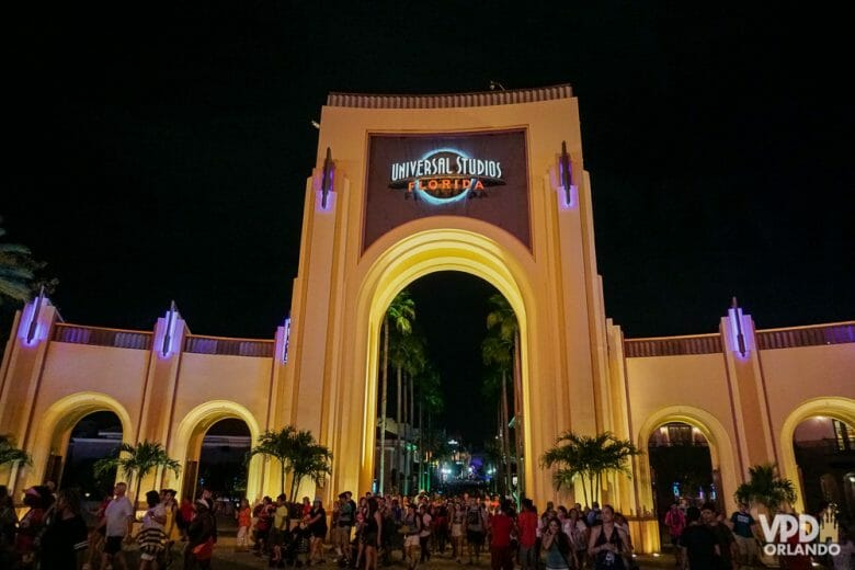 """Foto do portal na lateral do Universal Studios, com o título """"Universal Studios Florida"""" iluminado, muitos visitantes transitando e o céu noturno ao fundo"""