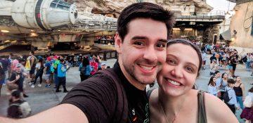 Foto da Renata e do Felipe sorrindo com a Millenium Falcon ao fundo na Star Wars Galaxy's Edge
